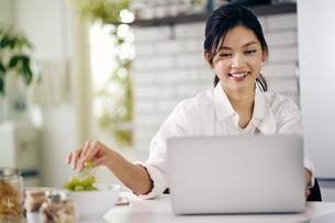 キッチンでノートパソコンを見る30代女性の写真素材 [FYI04589922]
