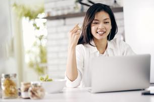 キッチンでノートパソコンを見る30代女性の写真素材 [FYI04589933]