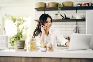 キッチンでノートパソコンを見る30代女性の写真素材 [FYI04589934]