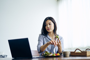 ノートパソコンを見ながら食事をする30代日本人女性の写真素材 [FYI04589956]