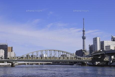スカイツリーをバックに隅田川を渡る総武線の写真素材 [FYI04589986]