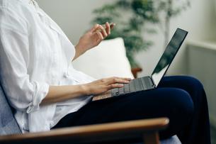 ノートパソコンでオンラインショッピングをする女性の写真素材 [FYI04589994]