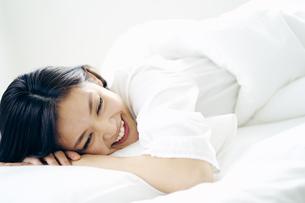 ベッドで横になる30代日本人女性の写真素材 [FYI04589999]