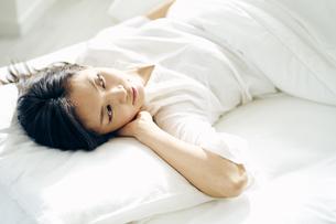 ベッドで横になる30代日本人女性の写真素材 [FYI04590001]