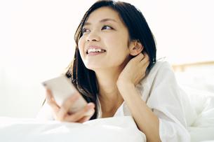 ベッドで横になってスマートフォンを見る30代日本人女性の写真素材 [FYI04590006]