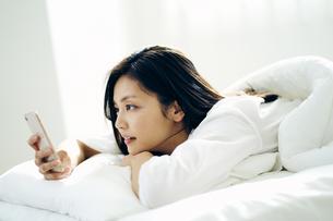 ベッドで横になってスマートフォンを見る30代日本人女性の写真素材 [FYI04590009]