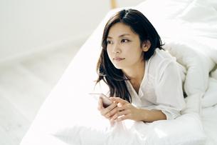 ベッドで横になってスマートフォンを持つ30代日本人女性の写真素材 [FYI04590013]