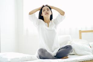 ベッドの上に座る30代日本人女性の写真素材 [FYI04590018]