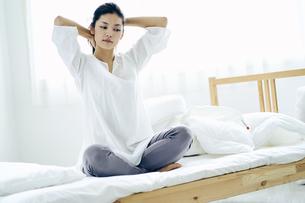 ベッドの上で髪を結う30代日本人女性の写真素材 [FYI04590019]