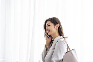 スマートフォンで話す30代ビジネスウーマンの写真素材 [FYI04590036]