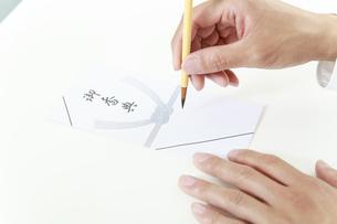 筆で香典に記名するイメージ。習字,仏事,アジアン・日本文化イメージの写真素材 [FYI04590117]