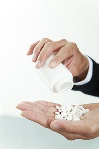 大量の錠剤を手の平に持つ男性の手アップの写真素材 [FYI04590124]