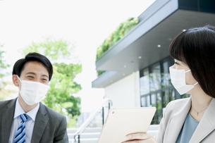 マスクをして打ち合わせをするビジネス男女の写真素材 [FYI04590127]