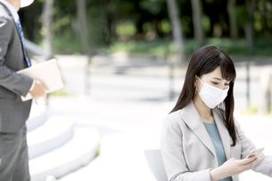 マスクをしたビジネスウーマンとタブレットを持つビジネスマンの写真素材 [FYI04590146]