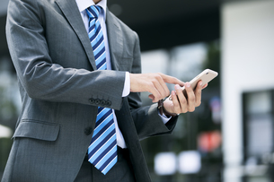 スマートフォンを操作するビジネスマンの手元の写真素材 [FYI04590248]
