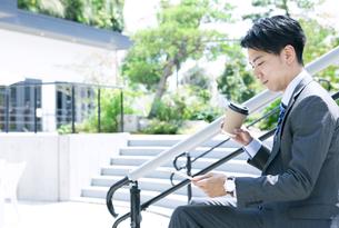 タブレットPCを見るビジネスマンの写真素材 [FYI04590258]