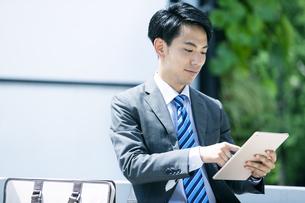 タブレットPCを操作するビジネスマンの写真素材 [FYI04590263]