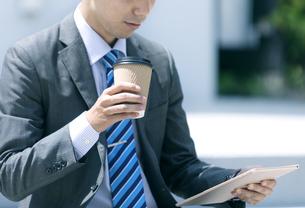 タブレットPCとドリンクを持つビジネスマンの写真素材 [FYI04590267]