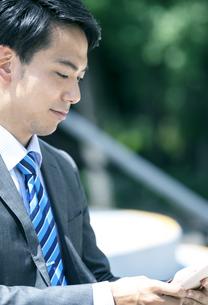 タブレットPCを見るビジネスマンの写真素材 [FYI04590268]