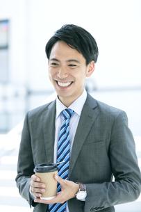 ドリンクを持つ笑顔のビジネスマンの写真素材 [FYI04590281]