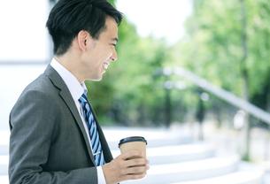 ドリンクを持つ笑顔のビジネスマンの写真素材 [FYI04590285]