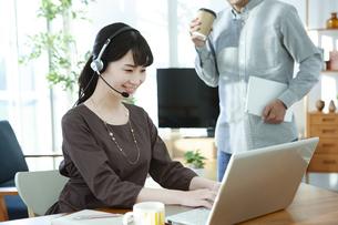 ノートパソコンを操作する女性とタブレットを持つ男性の写真素材 [FYI04590364]
