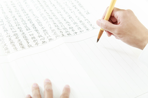 筆を持ち写経をする手元のクローズアップの写真素材 [FYI04590709]