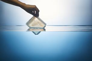 水の中からゴミを拾い上げる手の写真素材 [FYI04591008]