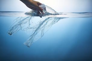 水中からポリ袋を拾い上げる手の写真素材 [FYI04591018]