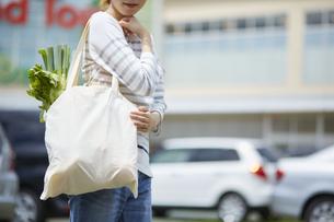 エコバッグに入れた食材を運んでいる女性の写真素材 [FYI04591022]