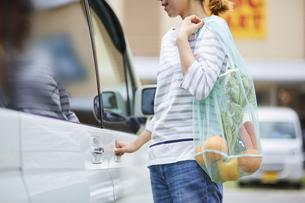 エコバッグを持って車に乗ろうとしている女性の写真素材 [FYI04591023]