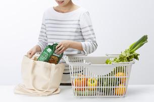 買い物カゴからエコバッグに食材を移す女性の写真素材 [FYI04591037]