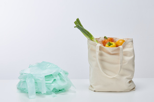 食材が入ったエコバッグと積み重なったレジ袋の写真素材 [FYI04591038]