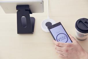 キャッシュレス決済端末にスマートフォンをかざしているところの写真素材 [FYI04591058]