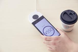 キャッシュレス決済端末にスマートフォンをかざしているところの写真素材 [FYI04591059]