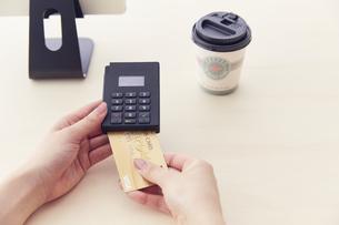 キャッシュレス決済端末にクレジットカードを差し込むところの写真素材 [FYI04591061]