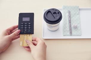 キャッシュレス決済端末にクレジットカードを差し込むところの写真素材 [FYI04591063]