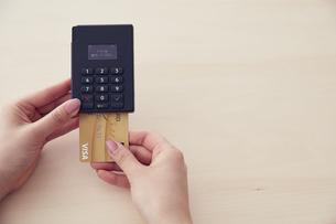 キャッシュレス決済端末にクレジットカードを差し込むところの写真素材 [FYI04591064]
