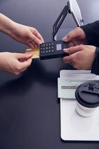 キャッシュレス決済端末にクレジットカードを差し込むところの写真素材 [FYI04591074]