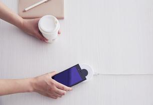 キャッシュレス決済端末にスマートフォンをかざしているところの写真素材 [FYI04591084]