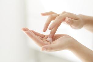化粧品を塗ろうとしている女性の手の写真素材 [FYI04591087]