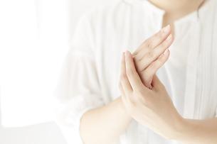 化粧品を塗っている女性の手の写真素材 [FYI04591093]