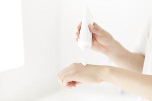 化粧品を塗っている女性の手の写真素材 [FYI04591094]
