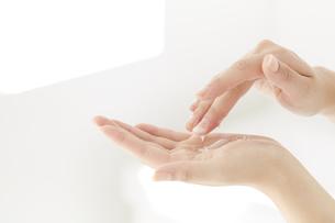 化粧品を塗っている女性の手の写真素材 [FYI04591095]