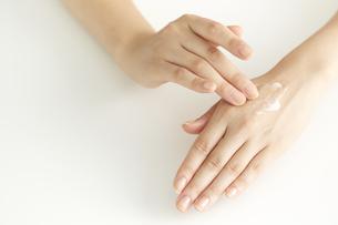 化粧品を塗っている女性の手の写真素材 [FYI04591108]