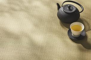 畳の上の鉄瓶と茶托に乗せたお茶の入った湯呑みの写真素材 [FYI04591125]