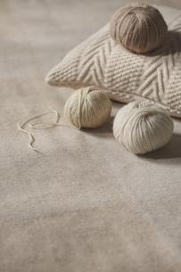 ニットのクッションの上に乗った毛糸玉と下に転がっている二つの毛糸玉の写真素材 [FYI04591137]