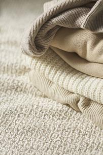 ベージュの生地の上に重なった五枚のセーターの写真素材 [FYI04591148]