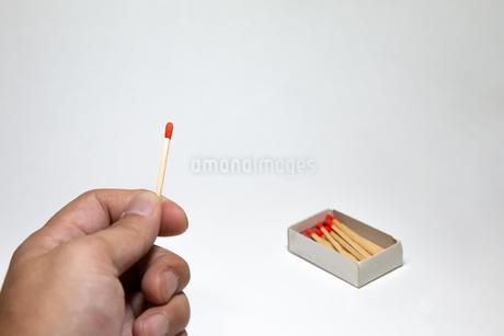 手に持ったマッチ棒とマッチ箱の写真素材 [FYI04591495]