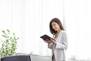 タブレットPCを見る30代ビジネスウーマンの写真素材 [FYI04591775]